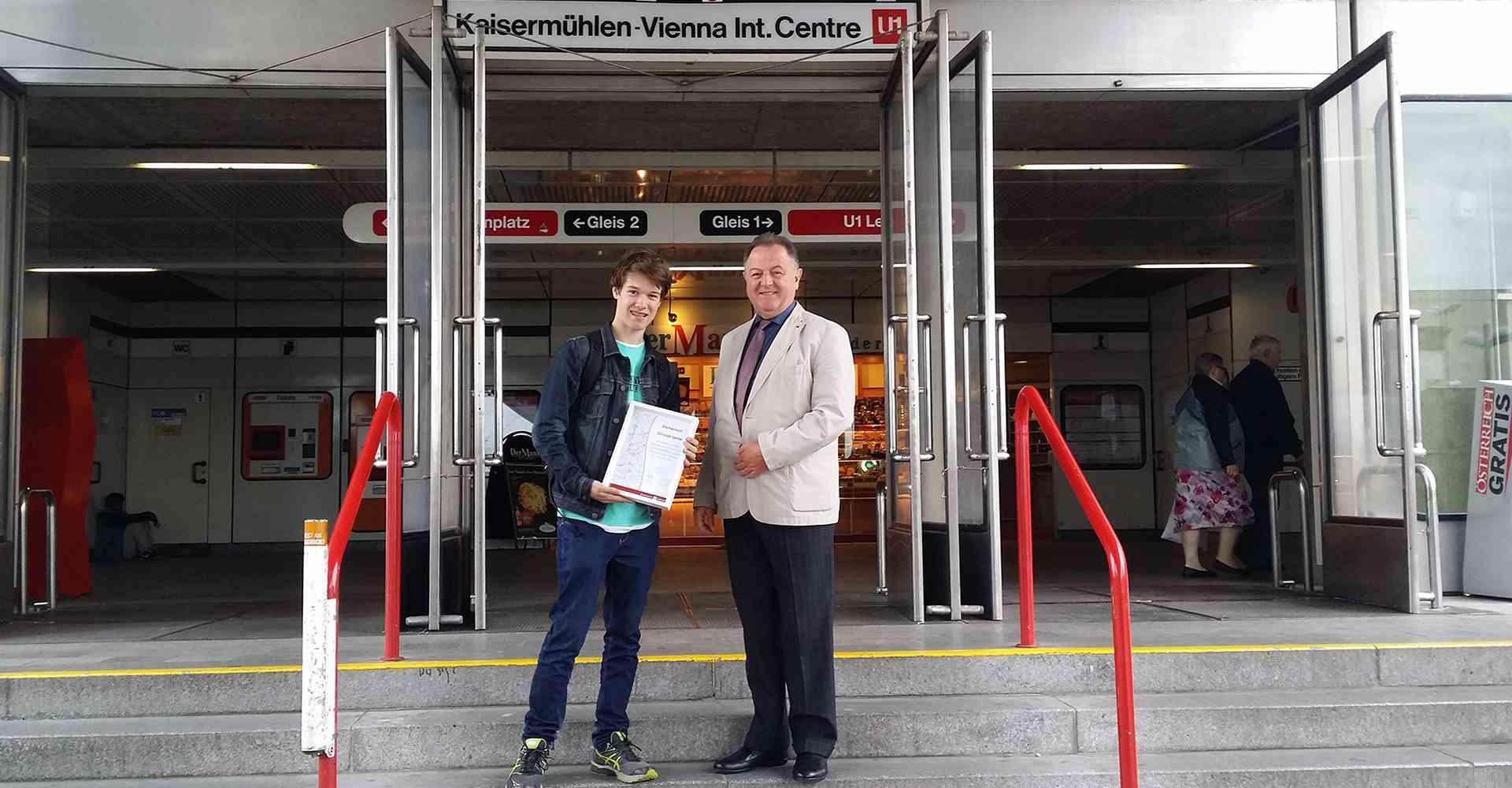 Wiener-Linien-Direktor Eduard Winter gratuliert Christoph bei seiner letzten Station, Kaisermühlen-VIC, und überreicht eine Urkunde.