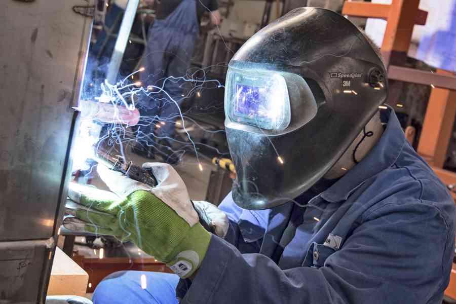 Arbeiter schweißen an einem Wagenkasten.