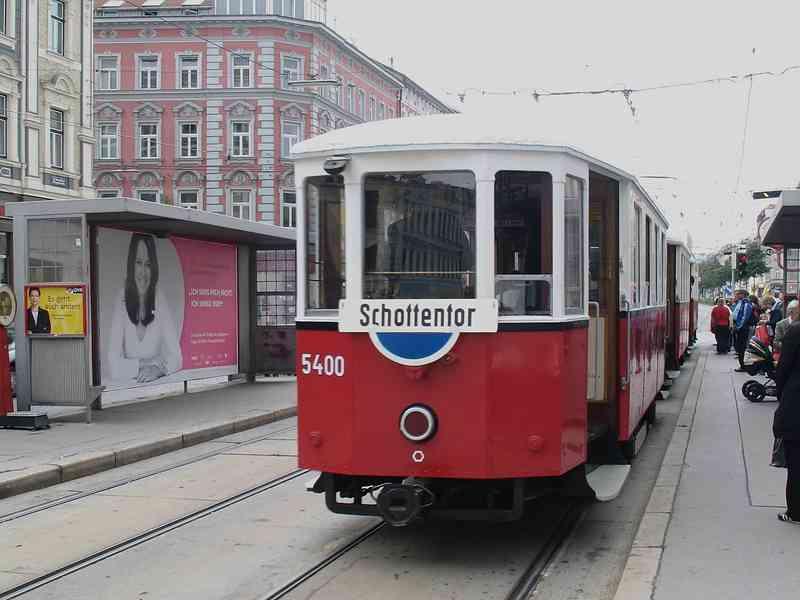 Eine historische Straßenbahn mit blauem Schild.